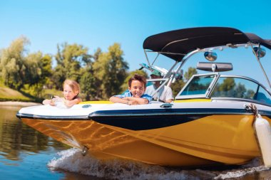 Cheerful little siblings enjoying view from boat bow