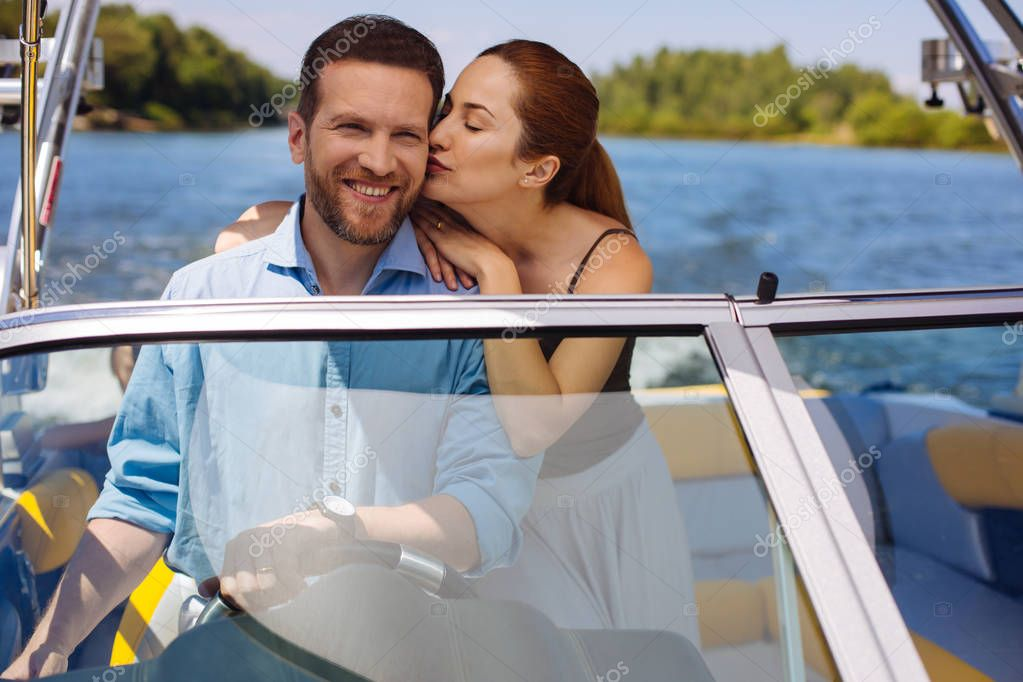 Affectionate young woman kissing husband sailing a boat