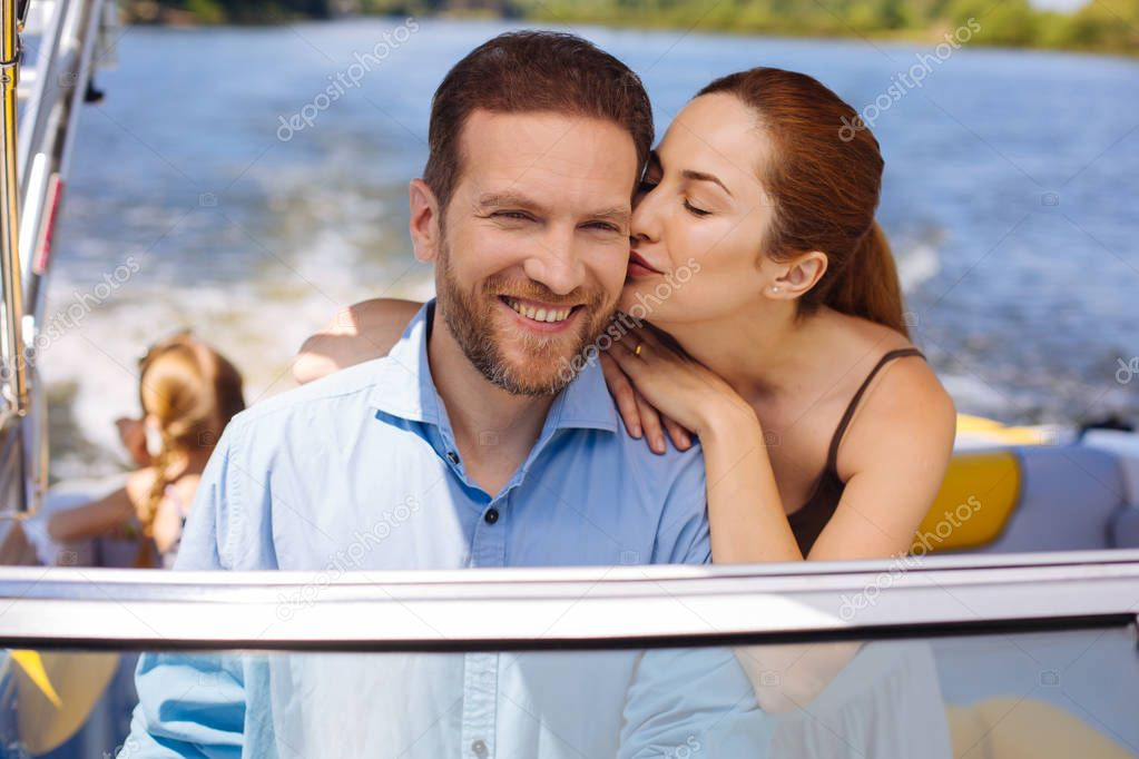 Happy husband. Joyful young man receiving a kiss on the cheek from his wife while sailing a boat during their vacation