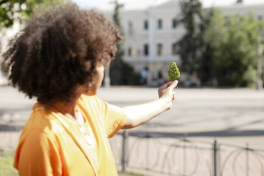 Curly-haired young woman holding tree model