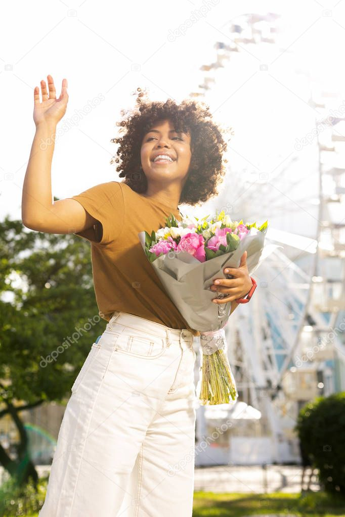 Pretty young woman waving to her date and holding flowers