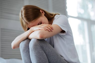 Miserable young woman crying at home