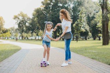 Pleasant stylish preschool girl having active walk with her mother