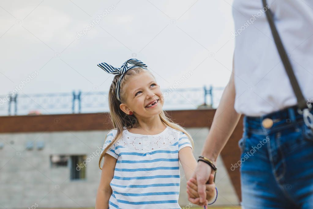 Smiling preschool daughter without teeth looking at her mother
