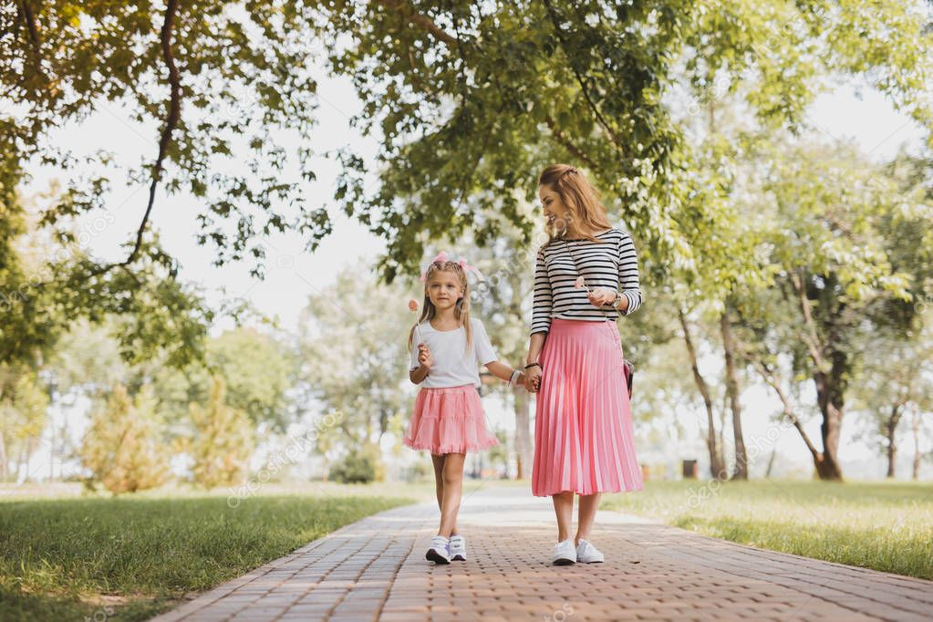 Blonde-haired daughter joining her mother in the park