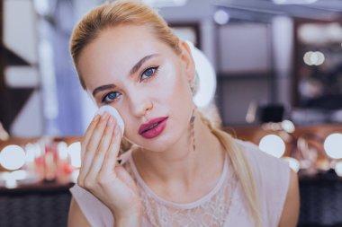 Beautiful woman wearing beige blouse taking her makeup off