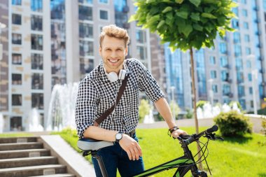Delighted pleasant man leaning on his bike