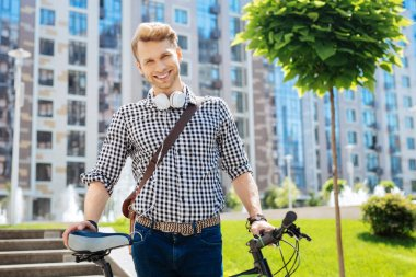 Pleasant nice man holding his bike