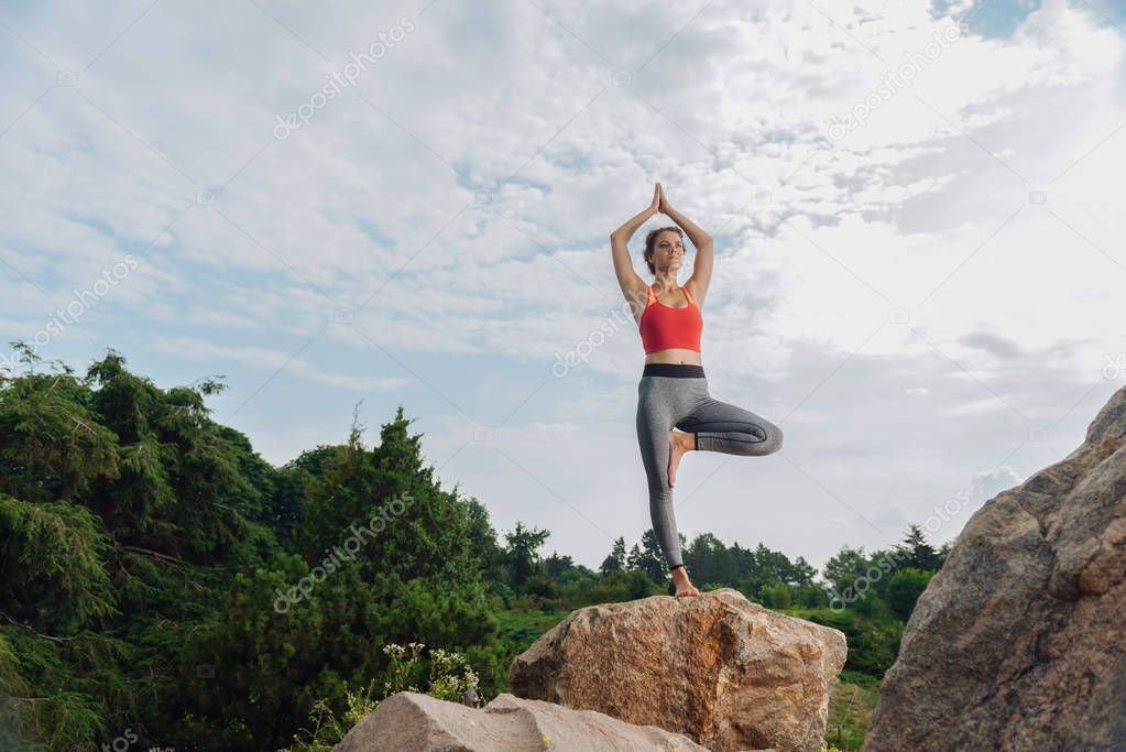 Fitness trainer practicing standing asana on the rock