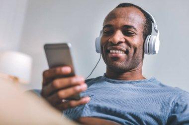 High-spirited man sitting in headphones