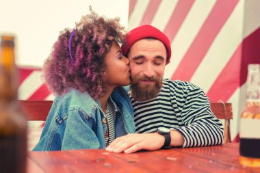 Cute young woman kissing cheek of her boyfriend and making him happy