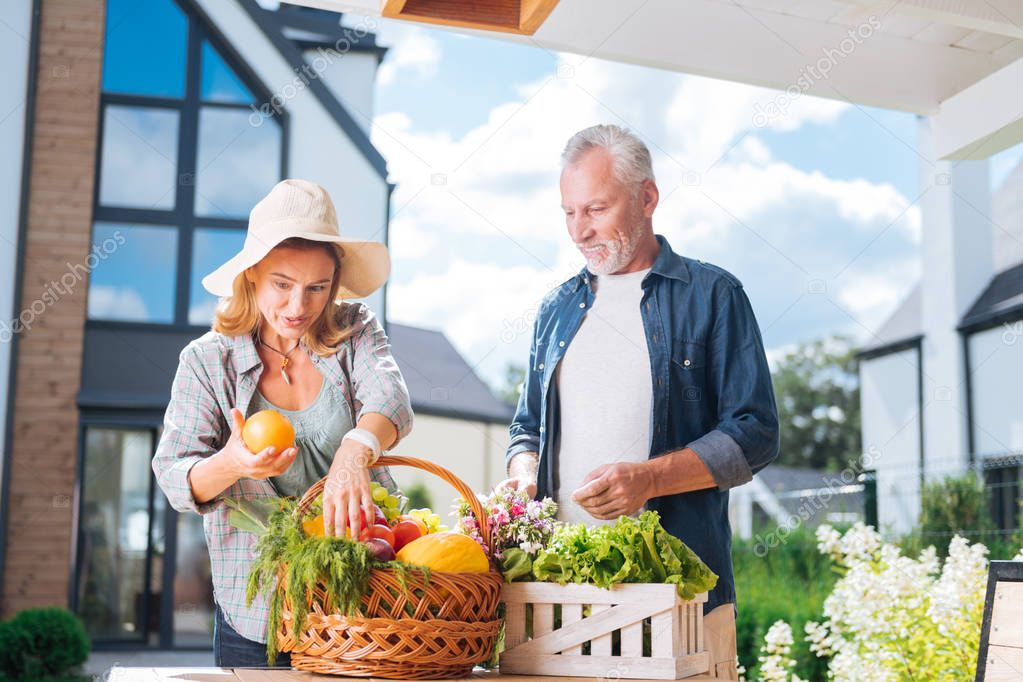 Appealing housewife holding nice fresh orange after buying food with husband