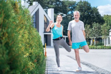 Slim healthy woman wearing grey leggings and blue shirt doing sport with husband