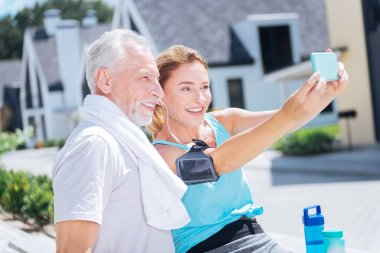 Smiling appealing woman holding blue phone while making photo with husband