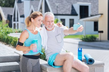 Bearded mature man holding his blue phone while making selfie with wife