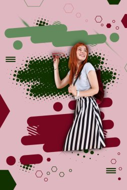Fashionable student. Fashionable red-haired cheerful student wearing striped skirt standing ahead of bright colorful ground