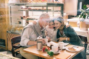 Loving granddaughter wearing white shirt hugging her grandparents