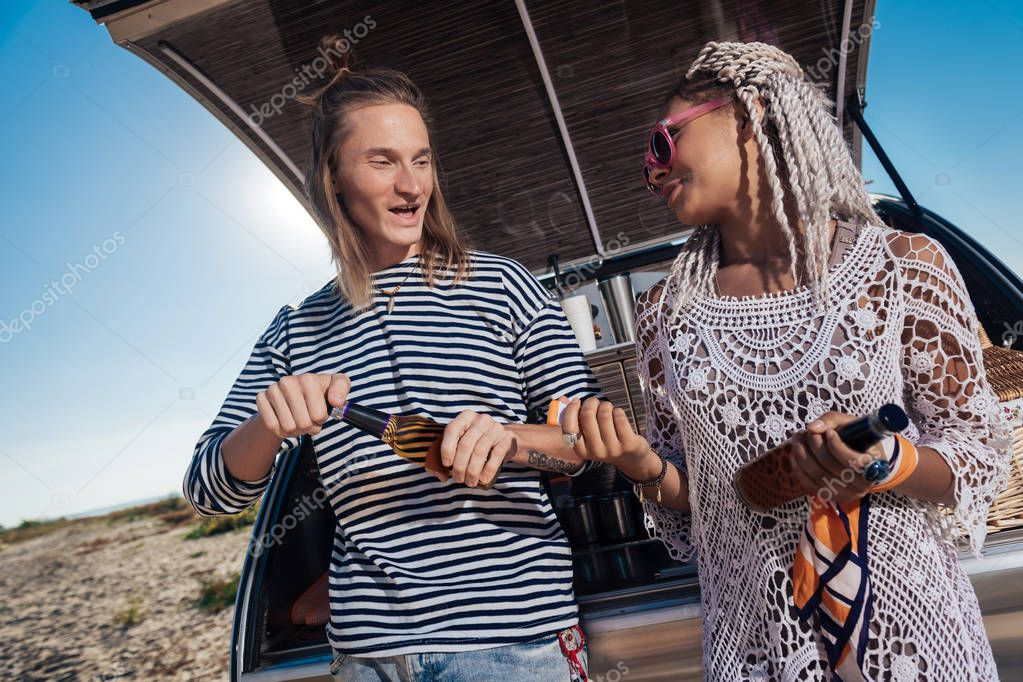 Stylish girlfriend with dreadlocks talking to her man drinking beer together