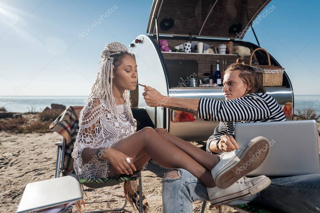 Blonde-haired man giving lighter his girlfriend smoking cigarette