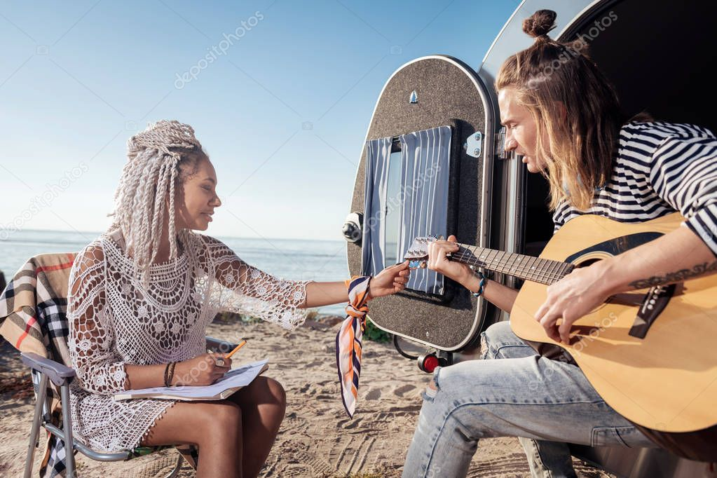 Girlfriend with white dreadlocks tuning the guitar for her boyfriend