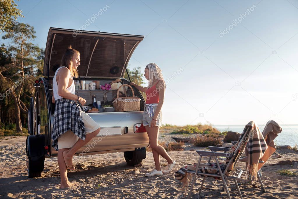Couple of travelers standing near their mobile home having breakfast