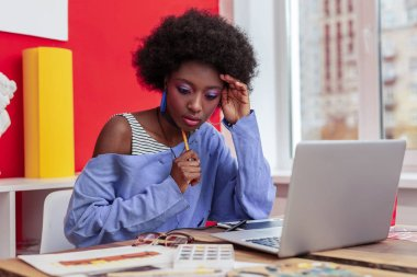 International student feeling busy writing e-mail to her professor
