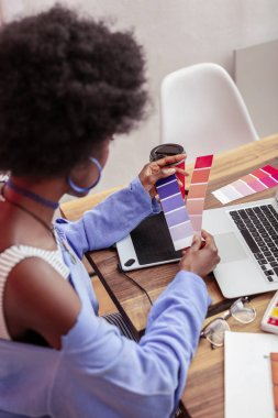 Young fashion designer holding color palettes while working
