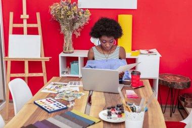 African-American designer wearing shirt with open shoulders