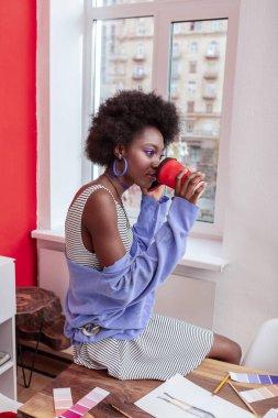 Slim stylish student sitting near the window and drinking coffee