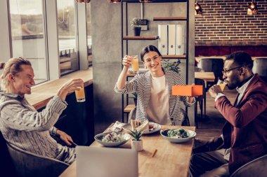 Cheerful young people drinking fresh orange juice