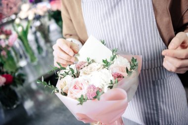 Natural beauty. Kind designer composing flowers, working in floral boutique