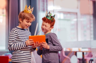 Young brave persons being crowned by each other