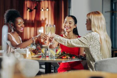 Three businesswomen clanging their glasses while celebrating Christmas