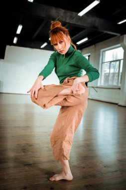 Red-haired professional choreographer with hair bun stretching her legs