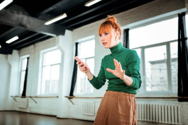 Red-haired professional yoga instructor in a green turtleneck holding a phone in her hand