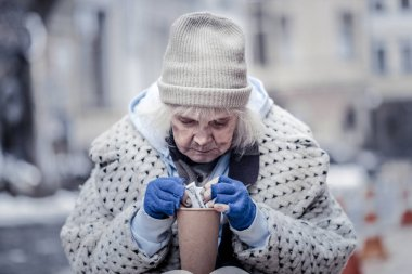 Nice homeless woman taking a hundred dollar banknote