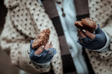 Close up of two bread pieces in female hands