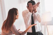 Fotografie Depressive Menschen schließt seine Augen, während seine wütende Frau schreien