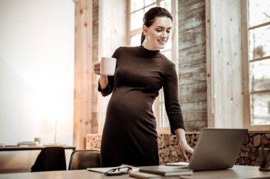 Joyful nice woman pressing a button on the laptop