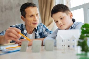 Pleasant father explaining principles of solar panels work