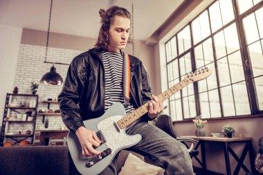 Rock musician wearing leather jacket playing favorite song