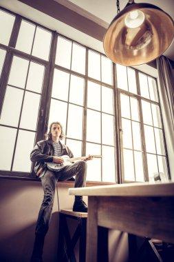 Slim rock musician wearing jeans sitting near window with guitar