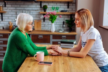 Upset sorrowful pensioner expressing emotions while talking to young lady