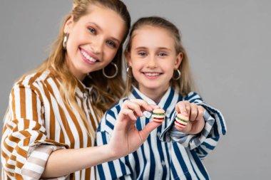 Joyful good-looking ladies presenting tiny burgers in their hands