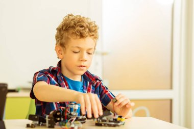 Best hobby. Intelligent cute boy building a robot while being interested in robotics science stock vector