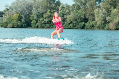 Young active beautiful blonde woman riding a wakeboard