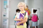 dunkeläugiger Junge im hellen T-Shirt, der zum Klassenzimmer läuft