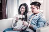 Pleasant couple spending time together with glasses of wine