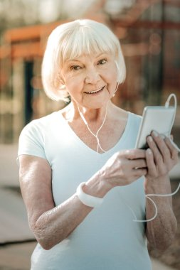 Keeping phone in hands. A nice old lady wearing workout clothing with a sincere smile and short grey hair keeping her phone in the hands being outdoor.