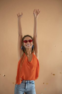 Smiling young African American raising her hands above her head under flying glitter